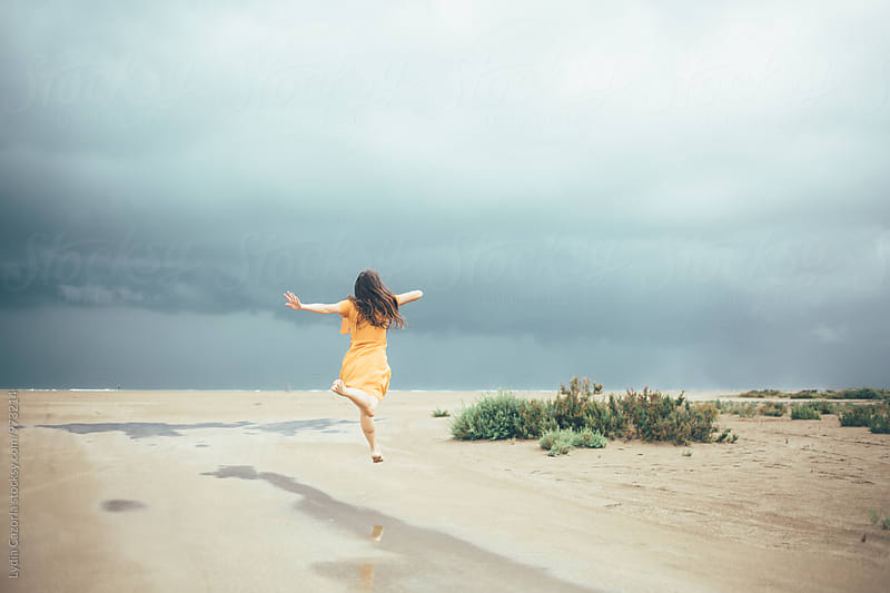 woman playing and jumping with water on the beach by Lydia Cazorla for Stocksy United