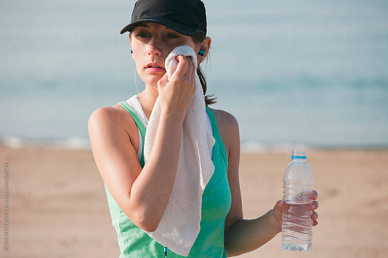 Sport girl drinking  water  after a run workout on the beach. by BONNINSTUDIO for Stocksy United