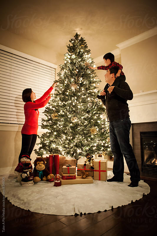 Asian family decorating Christmas tree with ornaments by Suprijono Suharjoto for Stocksy United