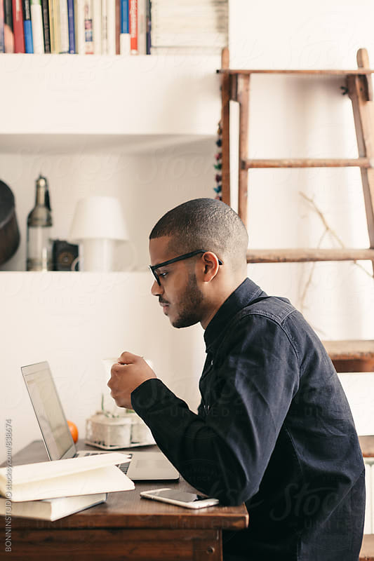 Side view of a latin man working with laptop at home office. by BONNINSTUDIO for Stocksy United