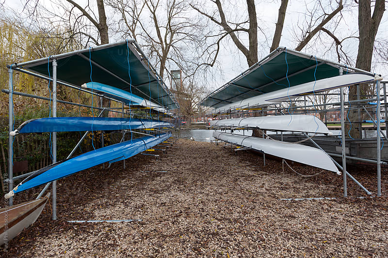 Six racing boats (Sculls) stored by the side of a river by Paul Phillips for Stocksy United