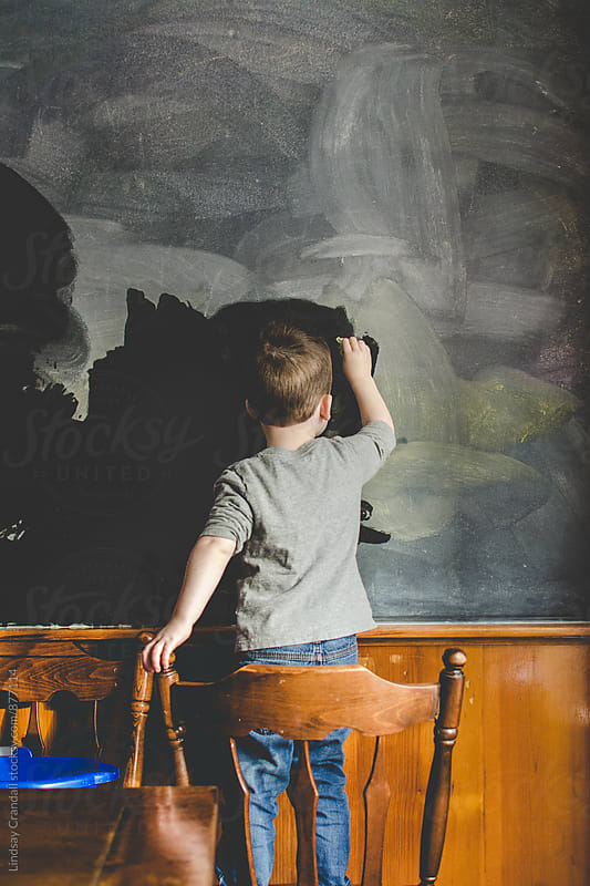 A child washing a chalkboard by Lindsay Crandall for Stocksy United