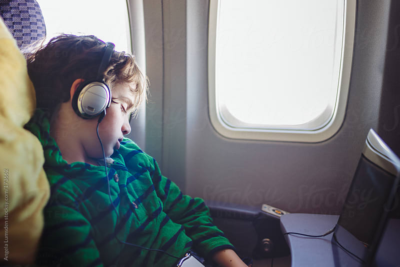 Boy sleeping on an airplane by Angela Lumsden for Stocksy United