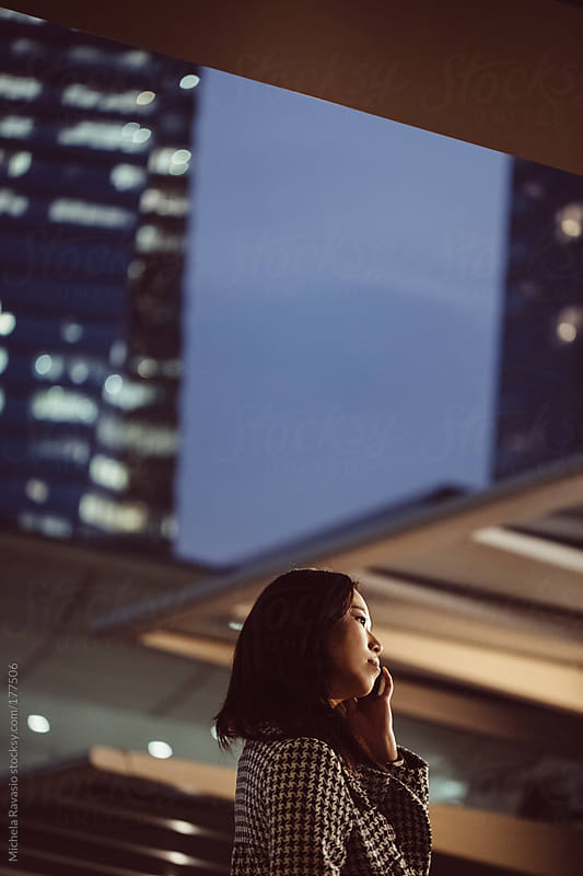 Young asian woman using her cell phone. by michela ravasio for Stocksy United