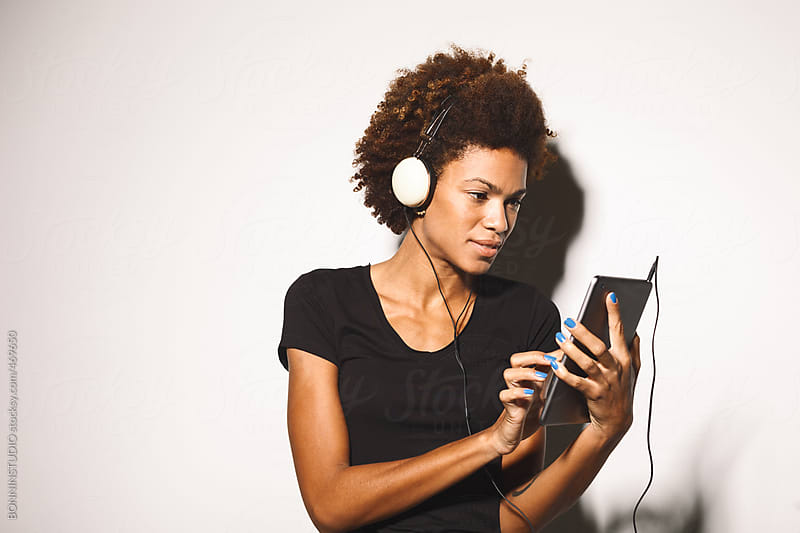 Young african american woman listening music on digital tablet against white background. by BONNINSTUDIO for Stocksy United