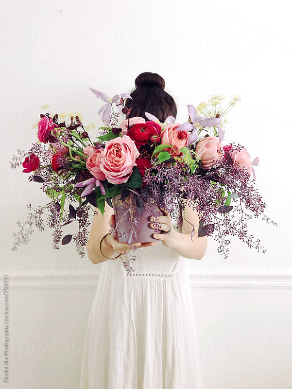 Woman holding bouquet of flowers by Daniel Kim Photography for Stocksy United