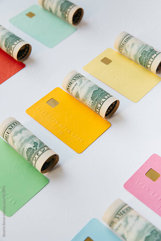 Concept for finance : dollar rolls and colorful credit cards by Beatrix Boros for Stocksy United