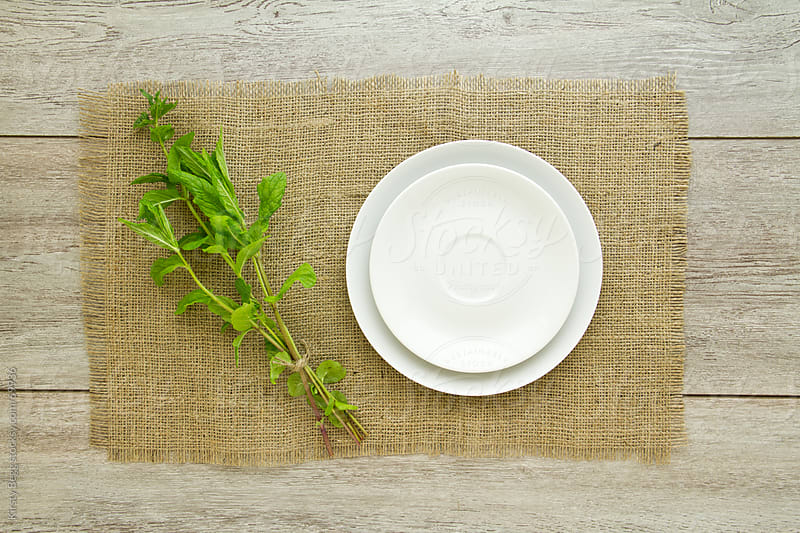 Empty plate with mint leaf stems on burlap by Kirsty Begg for Stocksy United