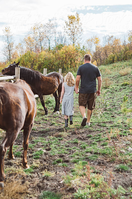 Father and daughter walking beside horses by Carey Shaw for Stocksy United
