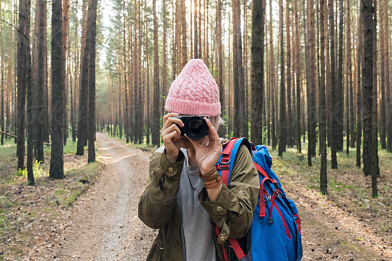 Young backpacker in pink hat photographing with camera by Danil Nevsky for Stocksy United