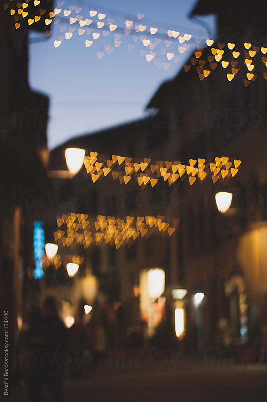 Defocused heart shape Christmas lights in the streets of Italy by Beatrix Boros for Stocksy United