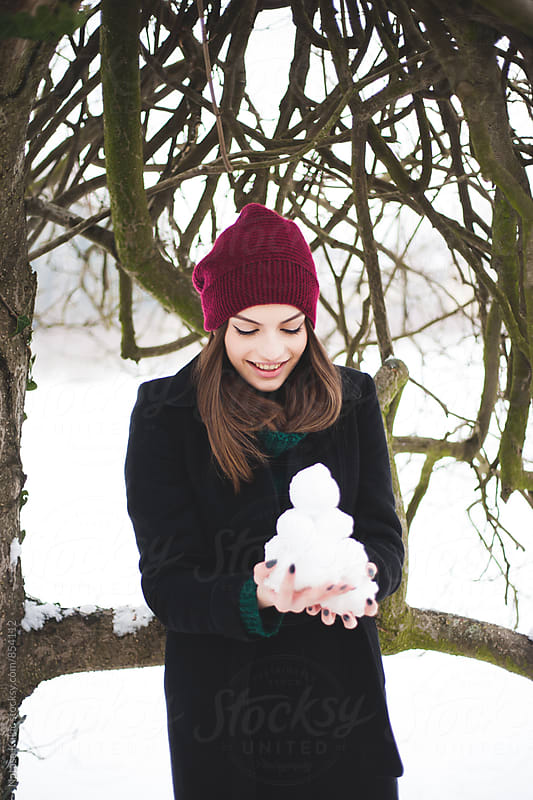 Winter portraits of a young beautiful woman holding snowballs by Natasa Kukic for Stocksy United
