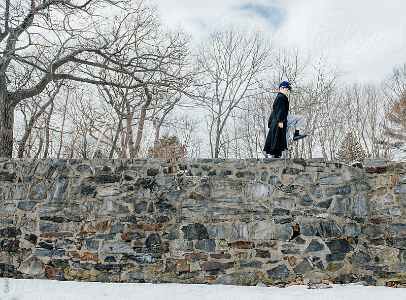 Boy pretending to be a Union soldier marches on a tall stone wall by Cara Dolan for Stocksy United