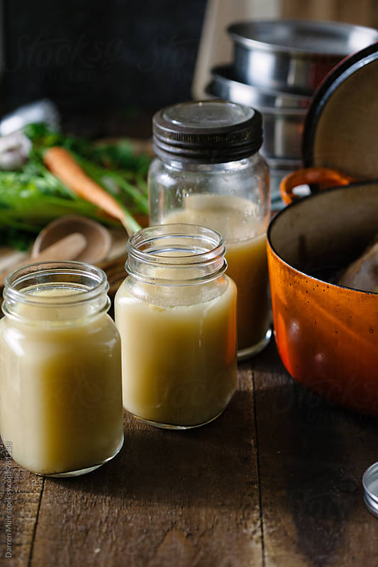 Bone broth: Freshly made bone broth in glass jars. by Darren Muir for Stocksy United