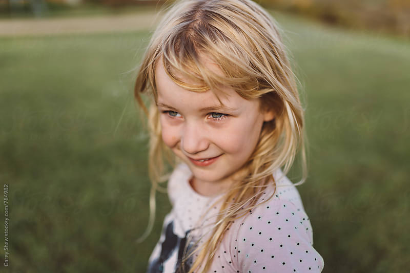Portrait of smiling young girl looking away by Carey Shaw for Stocksy United