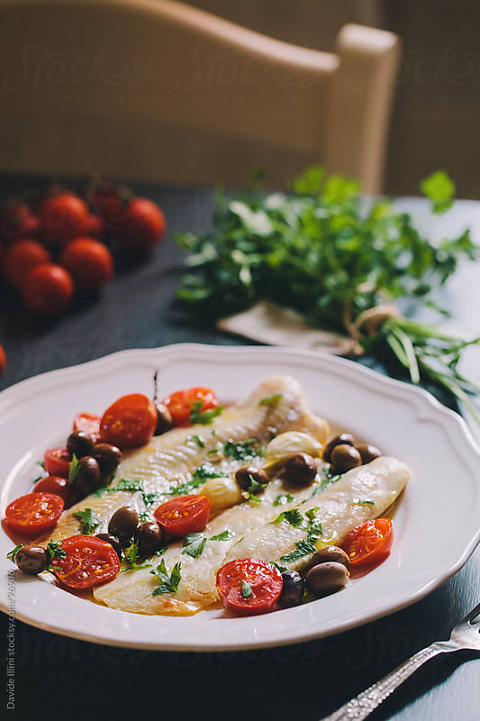 Fish fillets with cherry tomatoes and black olives by Davide Illini for Stocksy United