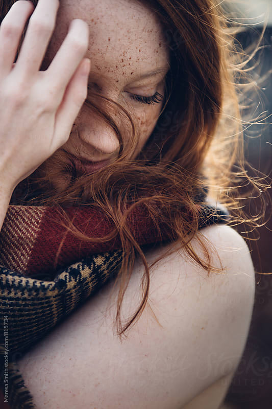 A girl on a windy day, holding her ginger hair from blowing in her face by Maresa Smith for Stocksy United