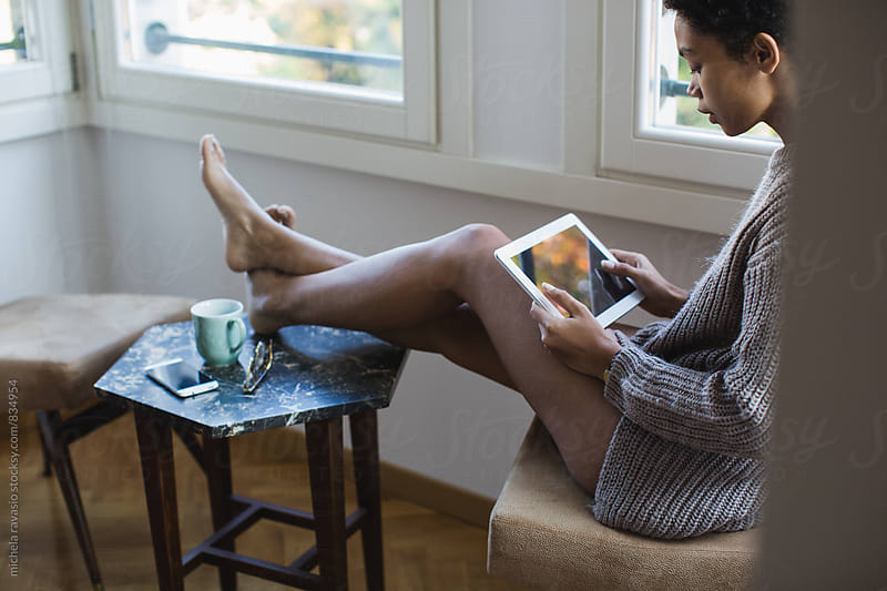 Relaxed woman holding digital tablet at home by michela ravasio for Stocksy United