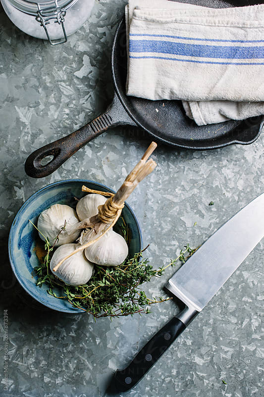 Garlic and thyme in a bowl on a metal table. by Darren Muir for Stocksy United