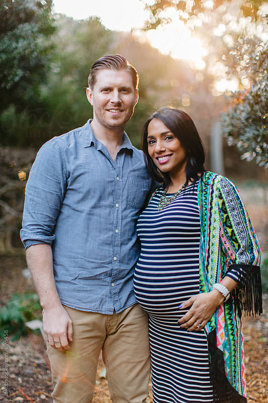 A beautiful pregnant woman standing next to her husband in a park by Jakob for Stocksy United