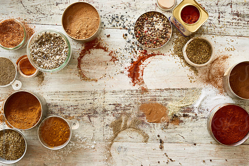 Variety of spices and seasoning on messy table by Trent Lanz for Stocksy United