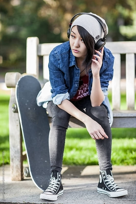 Asian college student listening to music by Suprijono Suharjoto for Stocksy United