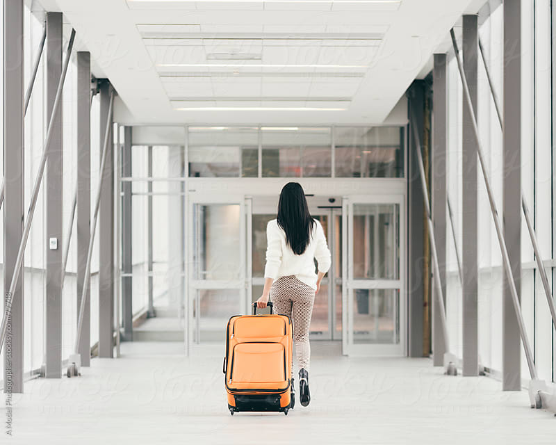 Girl with a suitcase in a hallway by Ania Boniecka for Stocksy United