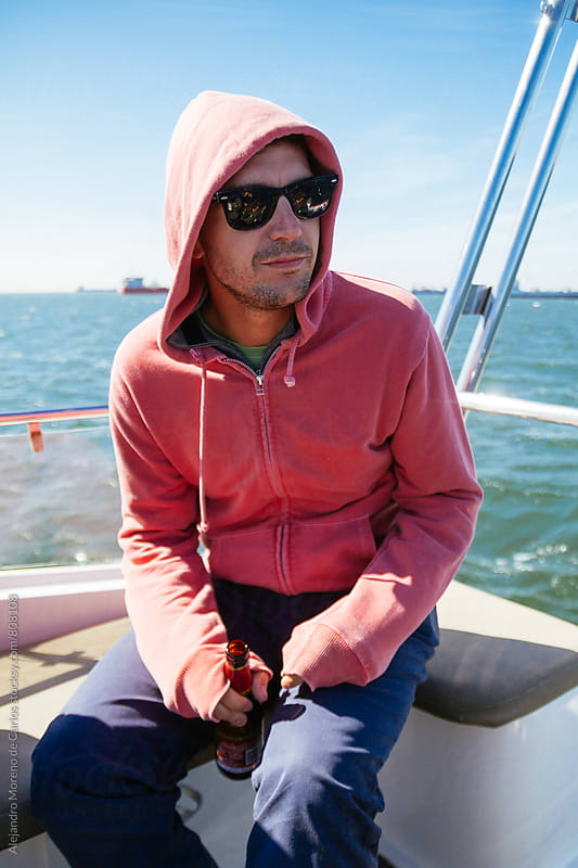 Young man wearing a hoddie sitting down in a sail boat on a cold clear sunny day by Alejandro Moreno de Carlos for Stocksy United