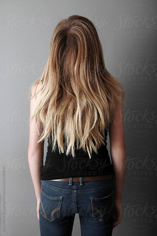 Backside of teenager with long hair wearing jeans and black tank top by Dina Giangregorio for Stocksy United