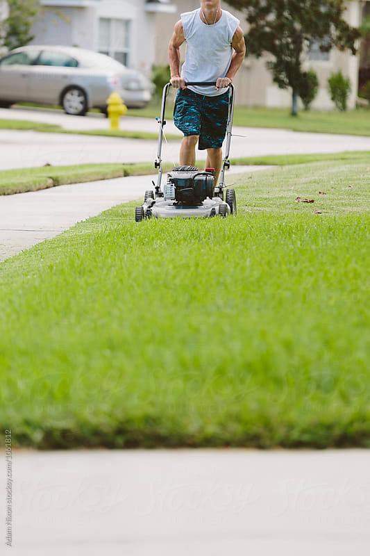Teenage boy mowing the lawn by Adam Nixon for Stocksy United