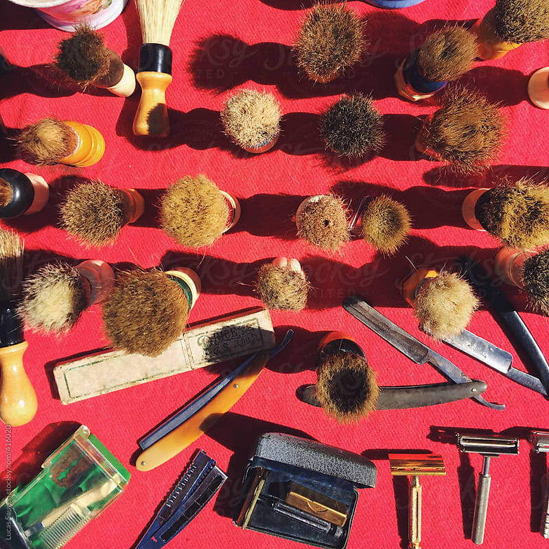 Looking down at vintage shaving razors and brushes on a red table. by Lucas Saugen for Stocksy United