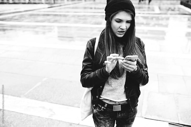 Beautiful young girl chatting on her smartphone by MEM Studio for Stocksy United