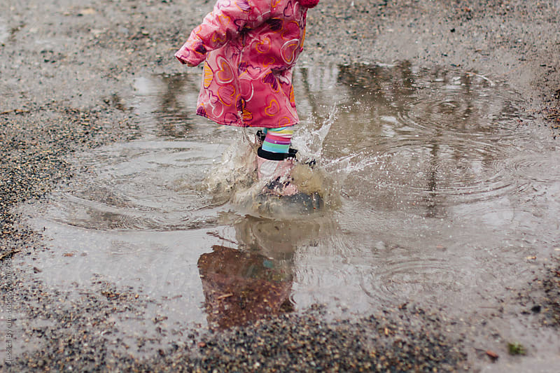 Small child in pink raincoat jumping in puddle by Jessica Byrum for Stocksy United