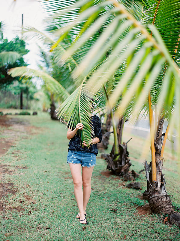 Woman behind palm tree by Daniel Kim Photography for Stocksy United