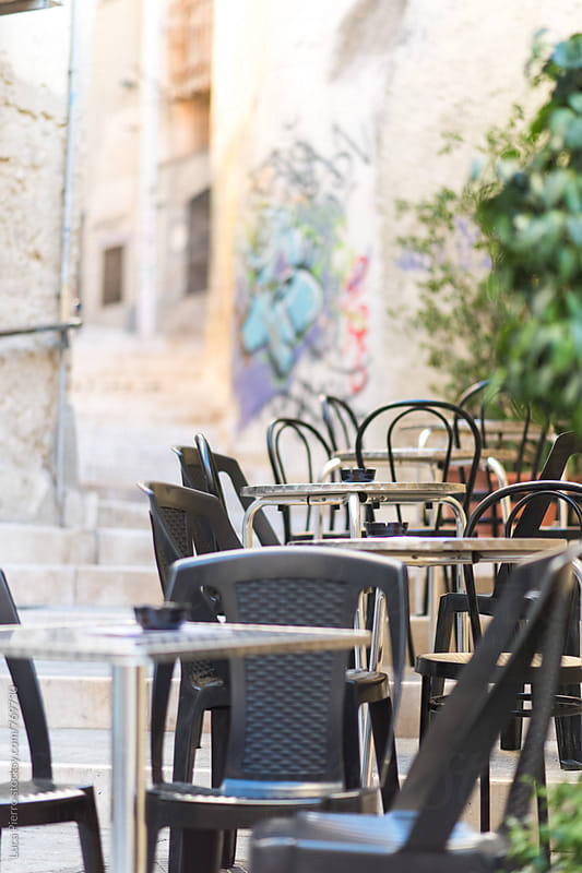Tables and chairs outside on a street by Luca Pierro for Stocksy United