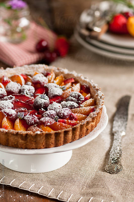 fruit tart with apricots cherries and strawberries by Laura Adani for Stocksy United