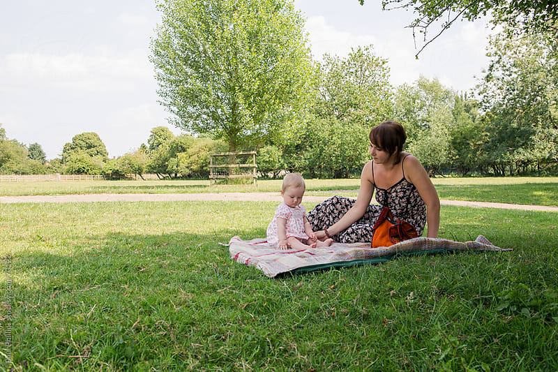Mother and child in parkland on a summer day by Paul Phillips for Stocksy United