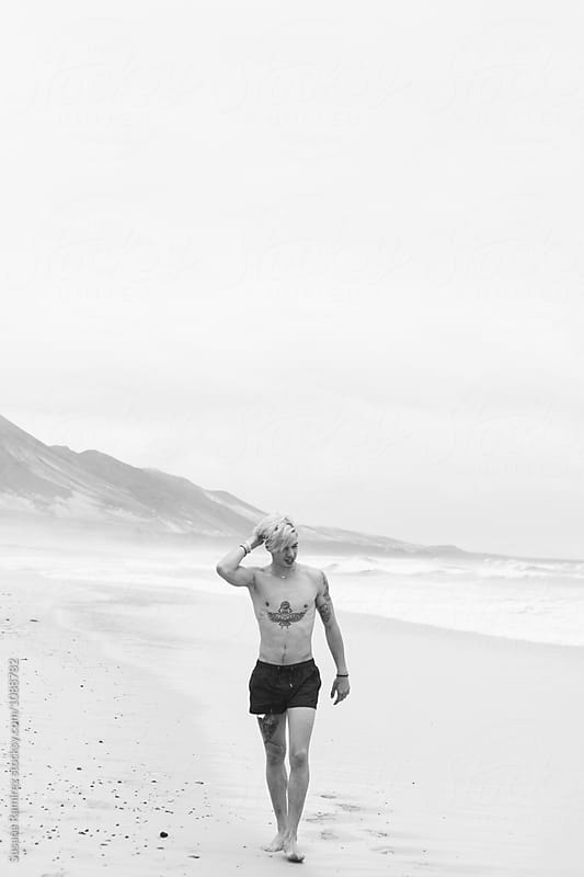 Man walking along the shore of the beach by Susana Ramírez for Stocksy United