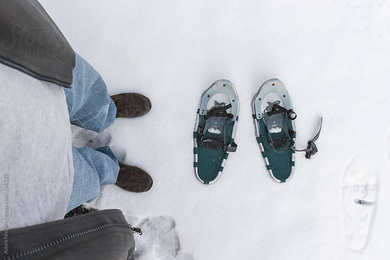 Man Standing over a pair of Snowshoes by Adam Nixon for Stocksy United