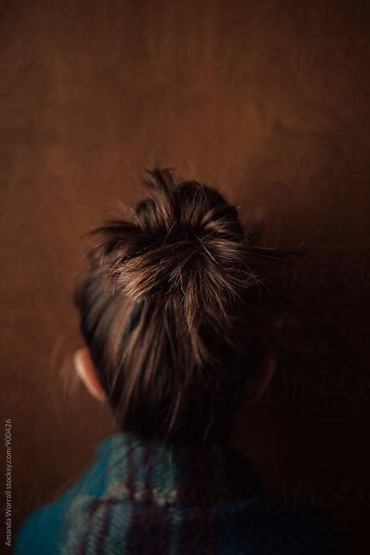 Back view of little girl with hair in a messy bun by Amanda Worrall for Stocksy United