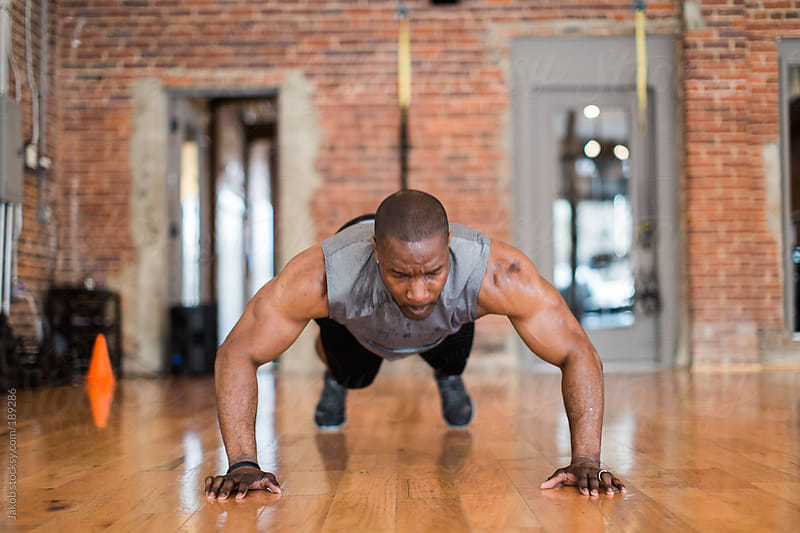 Muscular African-American man doing push-ups by Jakob for Stocksy United