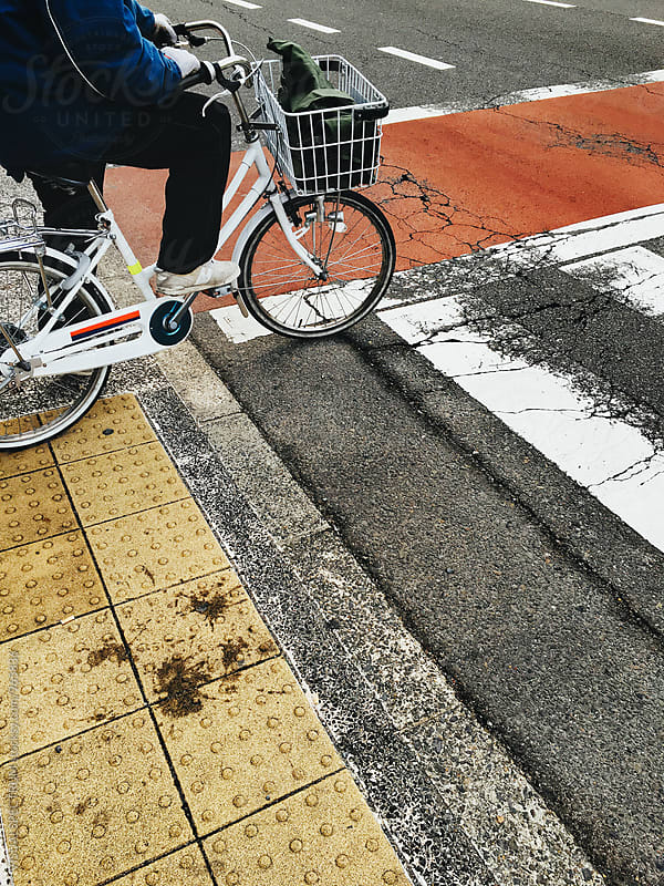 Old Person on Bicycle on Zebra Crossing in Japan by VISUALSPECTRUM for Stocksy United