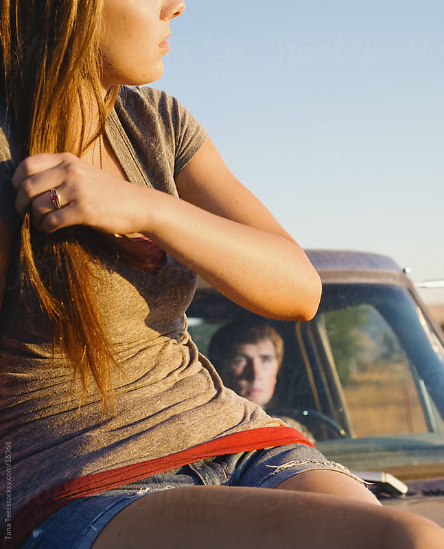 A young woman sitting on pickup in the sun. by Tana Teel for Stocksy United