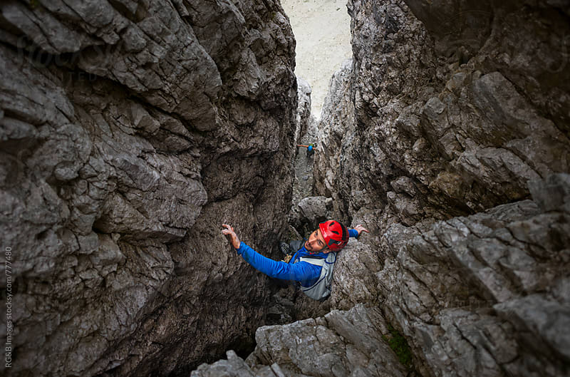 Alpinist rock climbing up a chimney crack outdoor by RG&B Images for Stocksy United