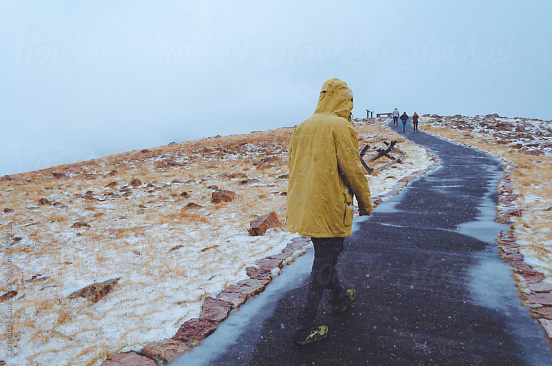 A man in a yellow winter jacket waling on a snowy path in the mountain by Constanza Caiceo for Stocksy United