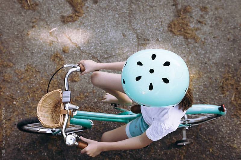 overhead view of a girl on a bicycle, with matching mint green helmet by Gillian Vann for Stocksy United