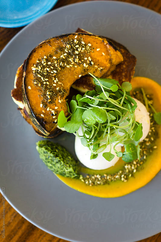 breakfast of poached eggs with roasted pumpkin, haloumi, dukkah  by Gillian Vann for Stocksy United
