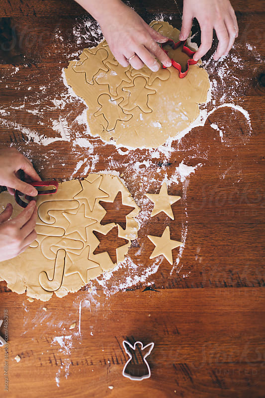 Hands of two girls cutting Christmas shapes out of biscuit dough by Jacqui Miller for Stocksy United
