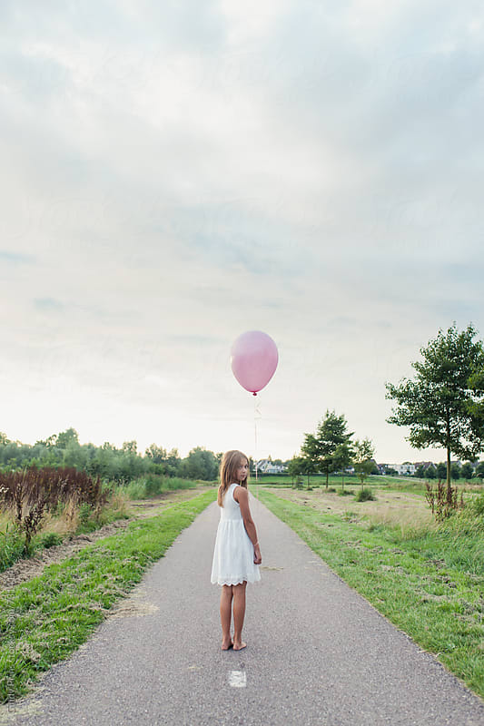 Little girl with a pink balloon standing on a long road looking backwards by Cindy Prins for Stocksy United