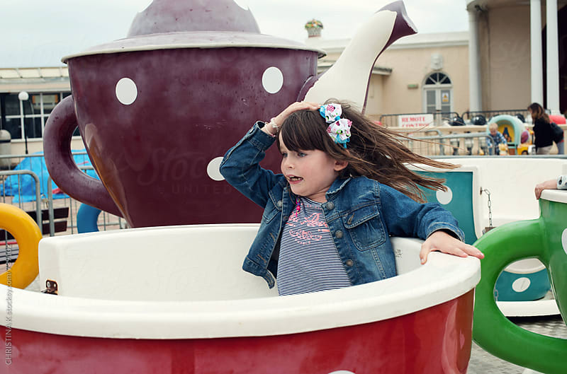 Little girl riding the teacups by Christina Kilgour for Stocksy United